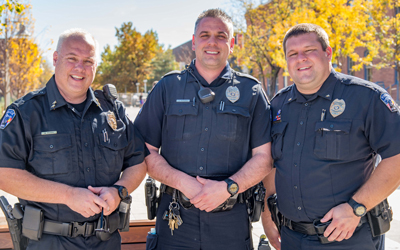 Auraria Campus Police Department officers stand on campus in front of the Tivoli on a fall day