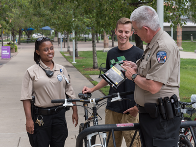 Two neighborhood community officers talk to a student about using a safer bike lock.