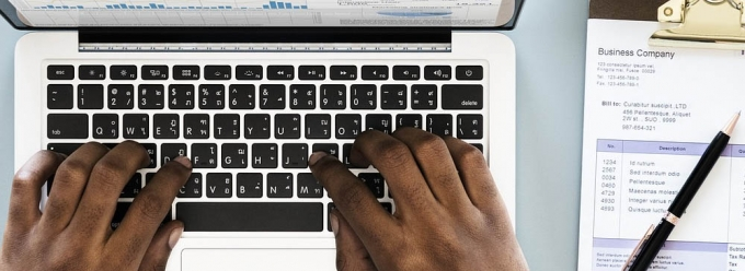 Hands typing on a laptop with a paper invoice nearby